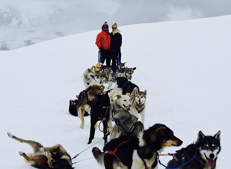 Couple with sled dogs on a glacier.