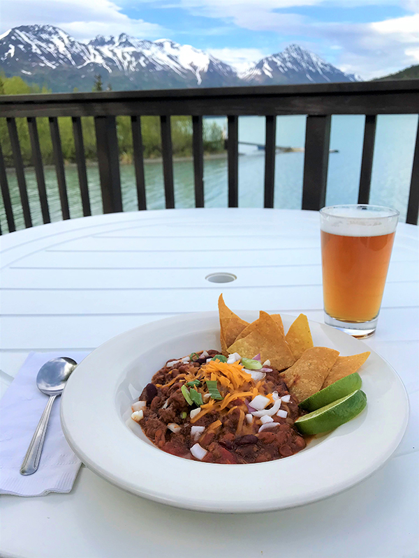 Chili and a beer on a balcony table.